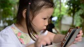 Little asian girl playing and touching a mobile phone