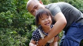 kız : Asian father playing with his daughter ,slow motion.