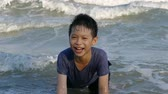 Happy asian boy in the surf on a summer beach,slow motion