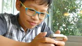 Asian boy playing games on smart phone Wideo