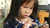 Little Asian girl playing games on smart phone