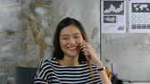 húszas évek : Beautiful Asian woman talking with friend by cellphone happily at office Stock mozgókép