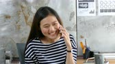 смеющийся : Beautiful Asian woman talking with friend by cellphone happily at office Стоковые видеозаписи