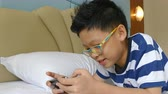 Young Asian boy playing games on smart phone in bedroom