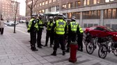 koruyucu : 4K Police bicycle team on standby at protest. A team of police officers wearing yellow safety vest talking near by their parked police bikes. Stok Video