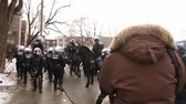 полиция : Riot police backs off while rioters shout at them. Rioters intimidate and push away police officers on horses.