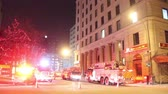 тендер : Fire trucks responding to an alarm call with multiple firetrucks in winter at night with old European looking building in the background