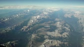 кокпит : Aerial view of vast mountain range on clear day. Pan motion while flying above the Rocky Mountains in a clear sky with a few clouds Стоковые видеозаписи