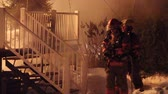 chamas : Firemen establishing fire attack plan. Two young fire fighters arrive at the scene of a house fire and determine a way to fight the blaze Stock Footage