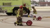 nem emberek : Drill crash victim transported on wheelbarrow An airport exercise fire fighter is carrying an actor on a wheel-barrow and rolling him away with airport fire appliance in the background