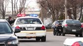 крейсер : 3 officers with guns drawn hiding behind police cars Multiple police officers with guns drawn hide behind police cruisers at daytime standoff incident. Стоковые видеозаписи