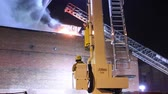 itfaiyeci : Fireman sits and controls articulating ladder truck Fireman sitting and controlling articulating platform from command seat with flames in the background Stok Video