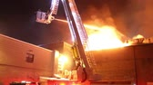 tomada : Firemen on articulating platform shooting water on fire Fire fighters in elevated fire apparatus put water on flames coming out of industrial building fire Stock Footage
