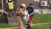 itfaiyeci : 4K Slow Motion - Fireman and policeman carrying elderly woman in their arms