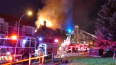 4K UHD - Police officer walking in foreground with house fire in background