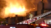 itfaiyeci : 4K UHD - Fire fighter walking down ladder with huge flames in background Stok Video