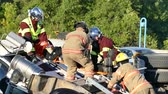 nurse : 4K UHD - Firemen and paramedics holding injured truck driver on spinal board