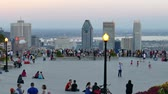 4K UHD - Kids playing on large observation deck with views on city at dusk