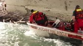 kurban : Water rescue crews pulling man out of water with heavy current into a boat Stok Video