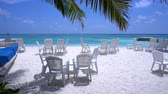 lunchroom : White plastic chairs and tables on sandy beach,