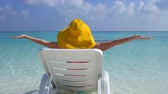 Woman in yellow sunhat sitting on sunbed and raising up hands