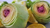 fruit vegetable : Cut fresh artichokes on plate with lemons