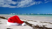 Christmas Santa Claus hat on tropical sandy beach with calm waves Wideo