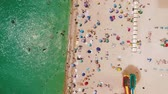 тент : Aerial view of the beach filled with people on a hot sunny day. Sun umbrellas stand in yellow bright sand. People rest and sunbathe on the beach on a summer day near the ocean. Стоковые видеозаписи