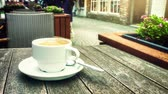 meal : Cup of coffee on wooden table. Bruges cityscape with horse drawn carriage. Full HD, 1080p
