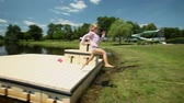 parent : Kid jumping onto grass near lake in France Stock Footage