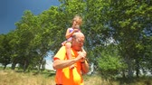 parent : Grandfather carrying grand daughter on shoulders in nature in summer