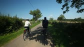 bike ride : Retired couple cycling on road in village in France