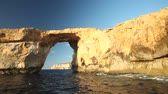 conhecido : Pan shot view of Azure Window, known as Tieqa erqa, a natural rock formation on the coast of Gozo island, Malta