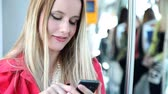 sedutor : Young blond woman riding tram, typing on mobile, phone, cell