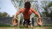close ups : Close up of muscular man doing push ups with gymnastics rings