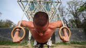 durability : Close up of muscular man doing push ups with gymnastics rings