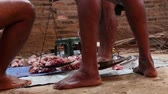 male animal : Men weighing meat of slaughtered animal.