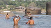xampu : HAMPI, INDIA - 28 JANUARY 2015: Men bathing and washing their hair in the river.