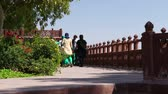 patio : JODHPUR, INDIA - 11 FEBRUARY 2015: Group of tourists walking by the fence of Jaswant Thada temple garden. Stock Footage