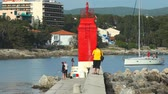 krk : KRK, CROATIA - MAY 4, 2013: Tourists walking on harbour wall on May 4, 2013 in Krk, Croatia. Ancient Krk town, is among the oldest cities in Adriatic, continuously inhabited since Roman times. Stock Footage