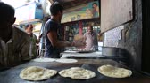 naan : MUMBAI, INDIA - 12 JANUARY 2015: Indian man preparing naan on grill in workshop in Mumbai.