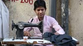 сшивание : MUMBAI, INDIA - 17 JANUARY 2015: Indian man working on a sewing machine.
