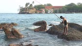 difícil : GALLE, SRI LANKA - MARCH 2014: Local fisherman fishing from a rock in Galle. These people find it more difficult to make a living due to over-fishing. Stock Footage