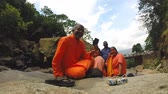 swami : ELLA, SRI LANKA - MARCH 2014: Religious group sitting on rocks at Ravana waterfalls.