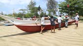 carry out : WELIGAMA, SRI LANKA - MARCH 2014: Fishermen pushing boat on sand into the ocean in Weligama. Stock Footage