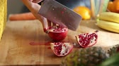 wood : Close-up of woman hands cutting pomegranate on wooden board, in slow motion