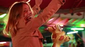 żyrafa : Close up of beautiful happy woman having fun riding carousel in amusement park, smiling and waving at camera