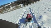 piekne : Father pulling daughter on sledge on snowly hill on sunny day