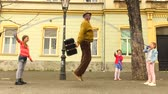 Old man jumping on a skipping rope with three girls in the street.