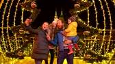 Family posing for photo in front of decoration at Christmas market.